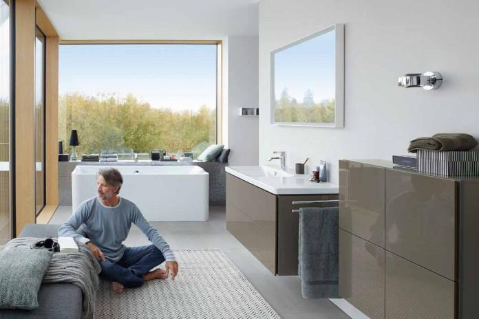 Mann der im modernen Bad im Schneidersitz auf dem Boden sitzt.