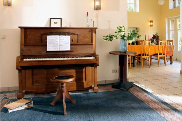 Das Klavier ist regelmäßig in Benutzung. Im Hintergrund das Esszimmer, fast ein Saal, in dem auch größere Gesellschaften Platz finden.