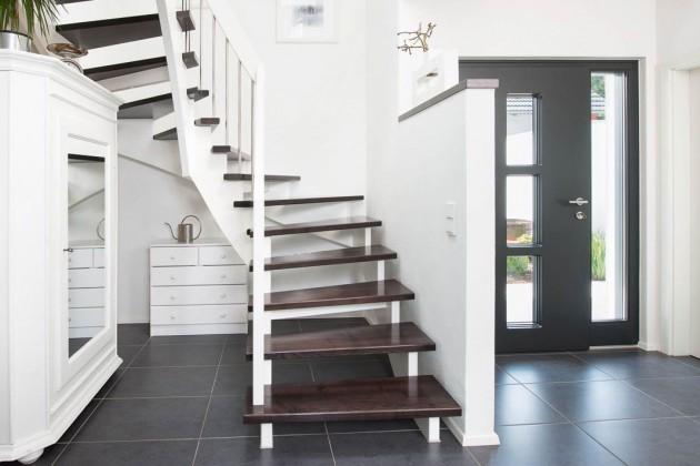 Eine dunkle Treppe mit weißem Geländer führt hinauf in das Dachgeschoss.