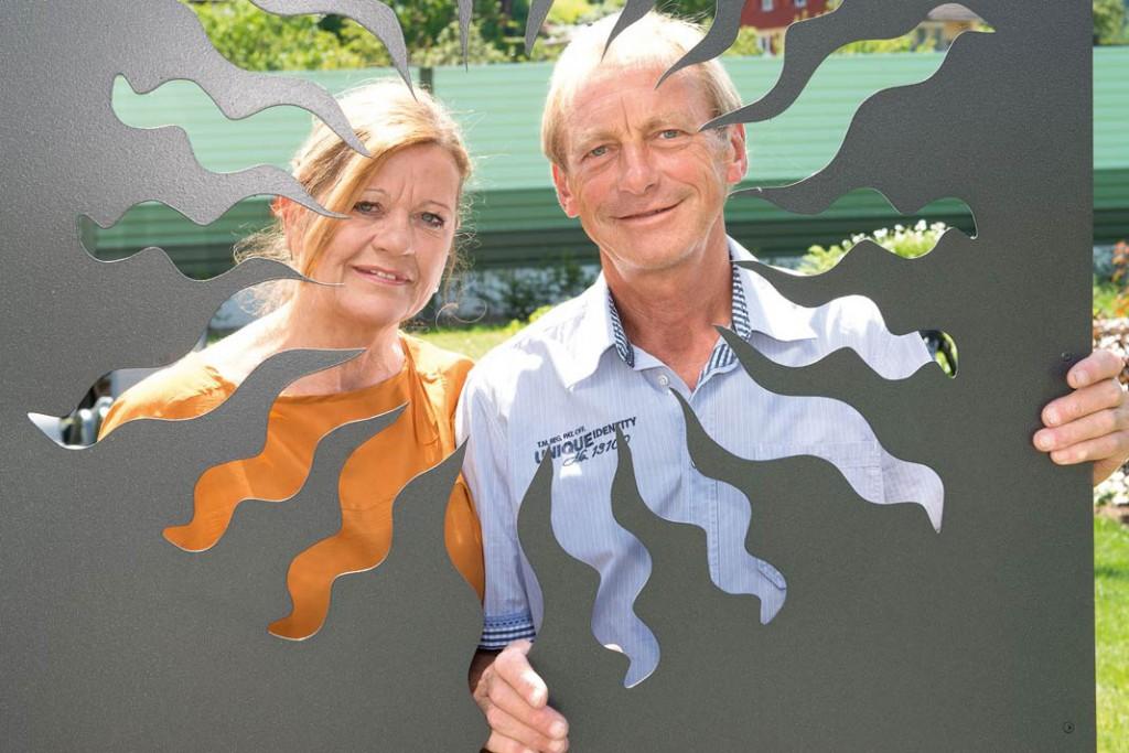 Bauherrenpaar Gudrun und Franz Spitz im Garten mit ihren selbst gestalteten Metallfiguren.