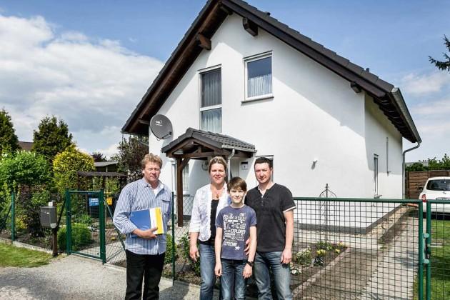 Jürgen, Gritta und Fiete Nörenberg mit ihrem Fachberater Volker Bürger (links) vor dem Neubau der Familie.