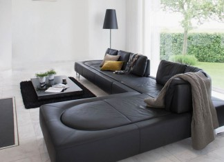 schwarzes Sofa mit Blick ins Grüne.
