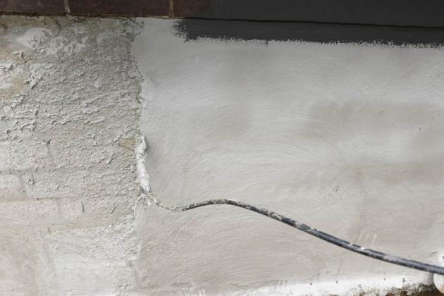 Der freigelegte Mauerwerk wurde in einem ersten Schritt mit einem Wasser-Sperrputz versehen.