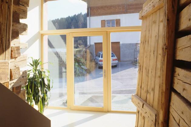 Alte Blockbohlenwände mit zeitgemäßer Belichtung – Blick vom Flur zum Eingangsbereich.