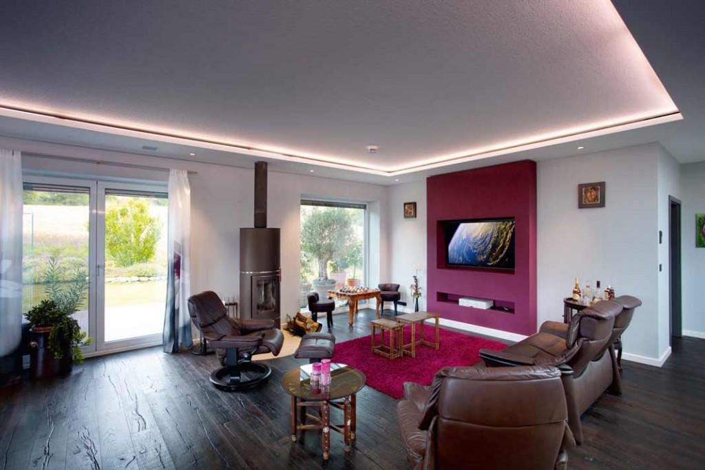 Clevere Details im Wohnbereich: die rote Fernsehwand lässt sich vorziehen, der Kamin leitet 60 Prozent seiner Wärmeenergie in den Wasserspeicher. Foto : Ulrich Beuttenmüller