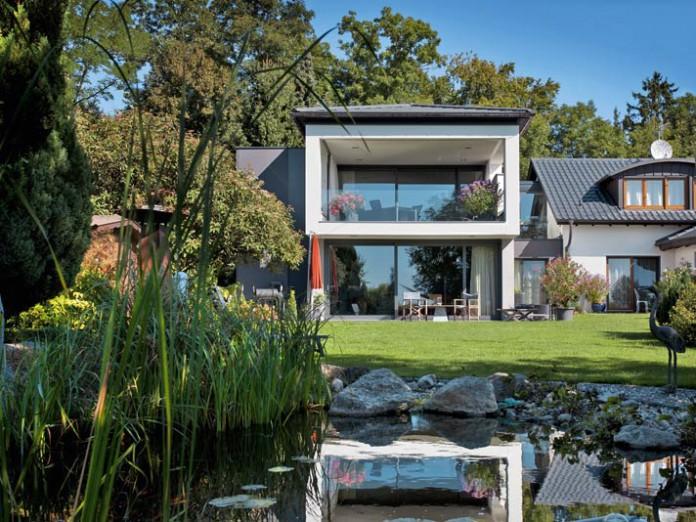 Der als moderner Kubus erstellte Anbau nutzt mit großflächiger Verglasung und dem auskragenden Balkon die Aussichtslage optimal.