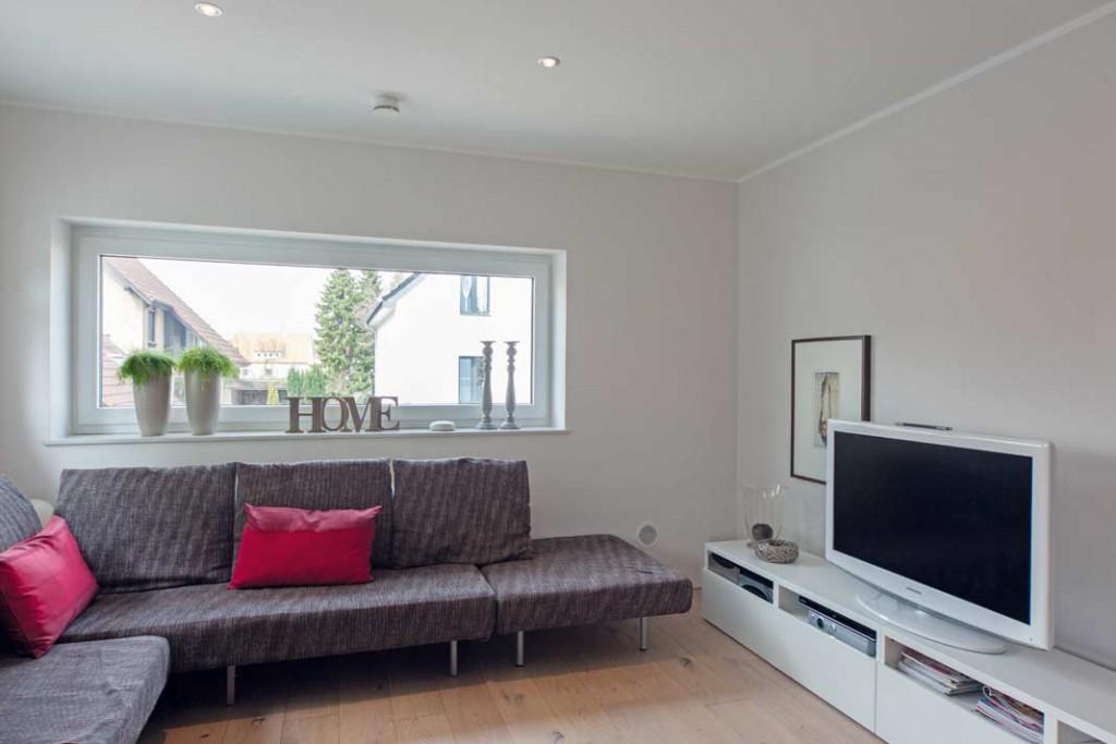 Durch ein kaum wahrnehmbares Zuluftgitter in Bodennähe strömt im Wohnzimmer (neben Couch rechts) die frische Luft zugluftfrei und lautlos in den Raum. Foto: Zehder