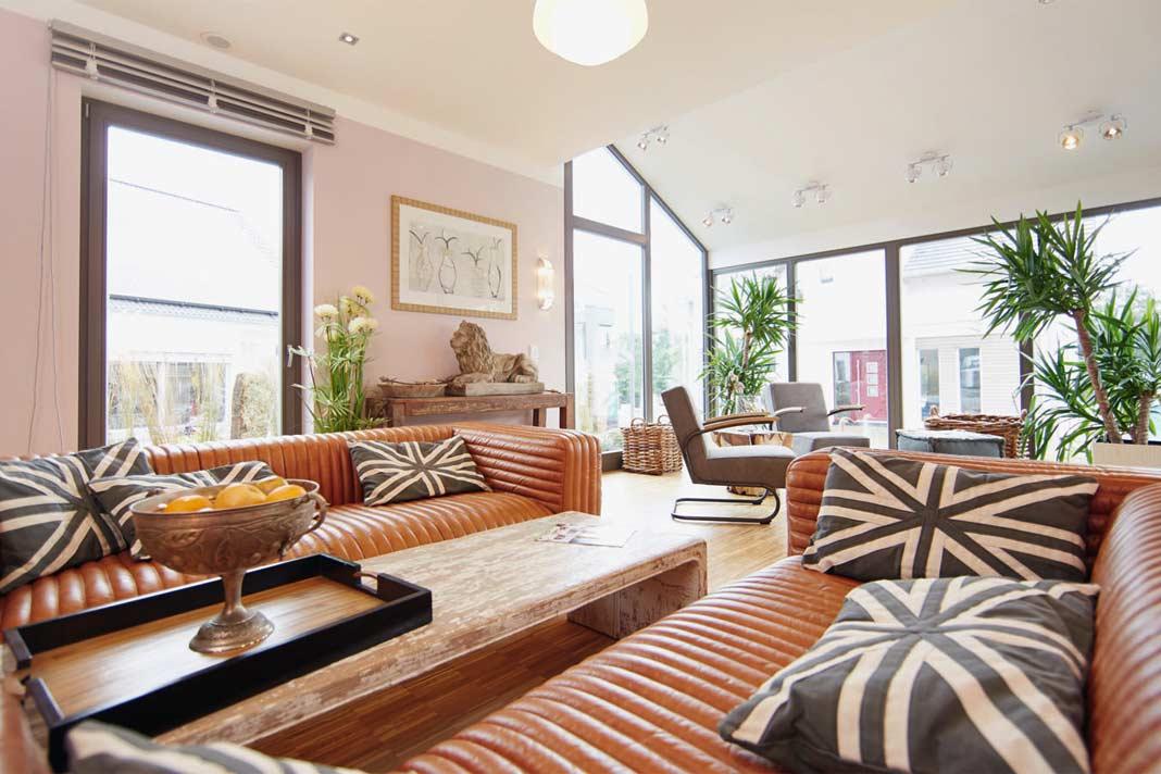 Das Wohnzimmer geht fließend in den Wintergarten über, wo sich die Familie eine licht - verwöhnte Relaxzone schaffen kann. Foto: Gusses