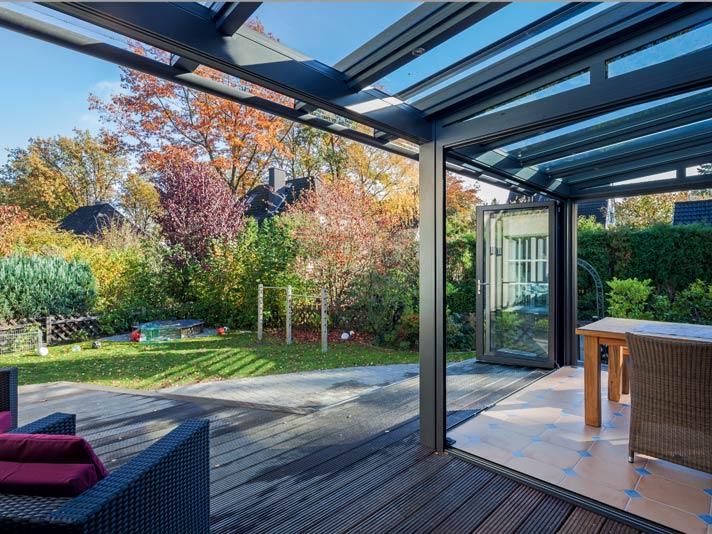 Der nachträglich angebaute Wintergarten besteht aus Glas-Faltwänden über alle drei Seiten.