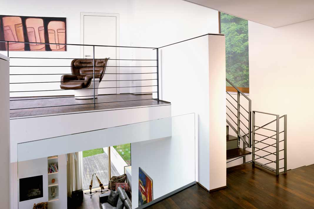 Treppe und Galerie: Wer nur konventionelles Bauen und Wohnen kennt, erlebt innen seinen kleinen Kulturschock.