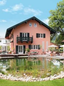 Haus mit angebauten Wintergarten und einem schön angelegten großen Teich.