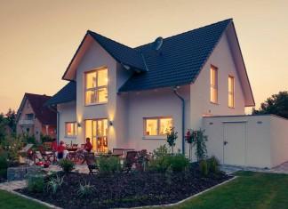 Am Abend leuchtet das Einfamilienhaus mit den großen Fensterflächen