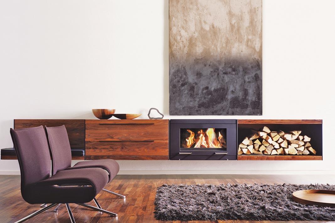 Hier verschmelzen Kaminofen mit Brennholz-Stauraumelement und Möbel zu einer Einheit und prägen damit innenarchitektonische Wohnszenen. Material: Nussbaum. Foto: Skantherm