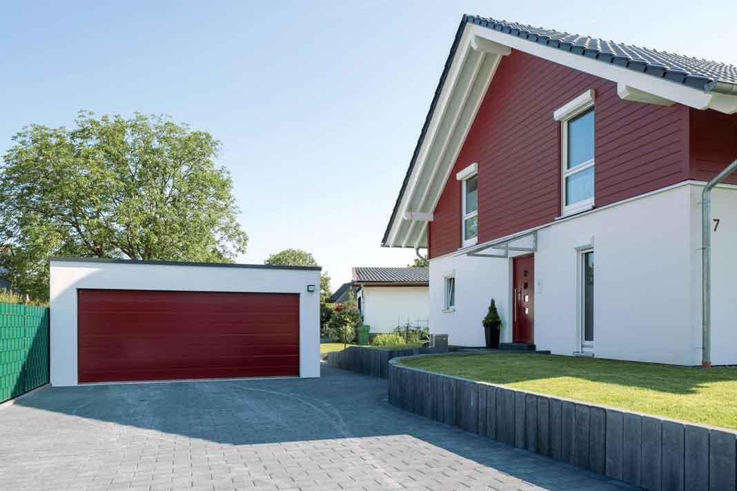 Perfekt abgestimmt: Haustür und Garagentor nehmen den Farbton der Fassade wieder auf. So entsteht ein harmonisches Ganzes. Foto: Frings