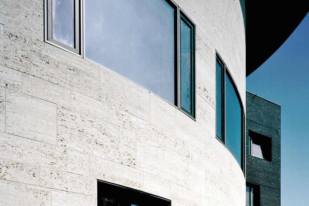 """Verschiedene Fassaden systeme bieten sich für eine moderne Gestaltung mit Naturstein an. Da kann sich die Fassade sogar """"in die Kurve"""" legen wie die des Frankfurter Kleist-Zentrums in sandgestrahltem Muschelkalk. Foto: Sto"""