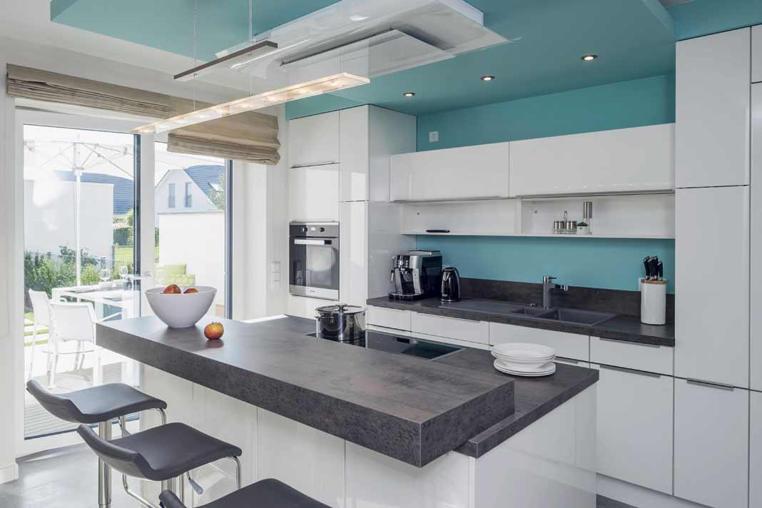 Die moderne Küche bietet an der Kochinsel Platz fürs schnelle Frühstück. Von hier aus gelangt man auch in den offenen Wohn- und Essbereich. Foto: Arge