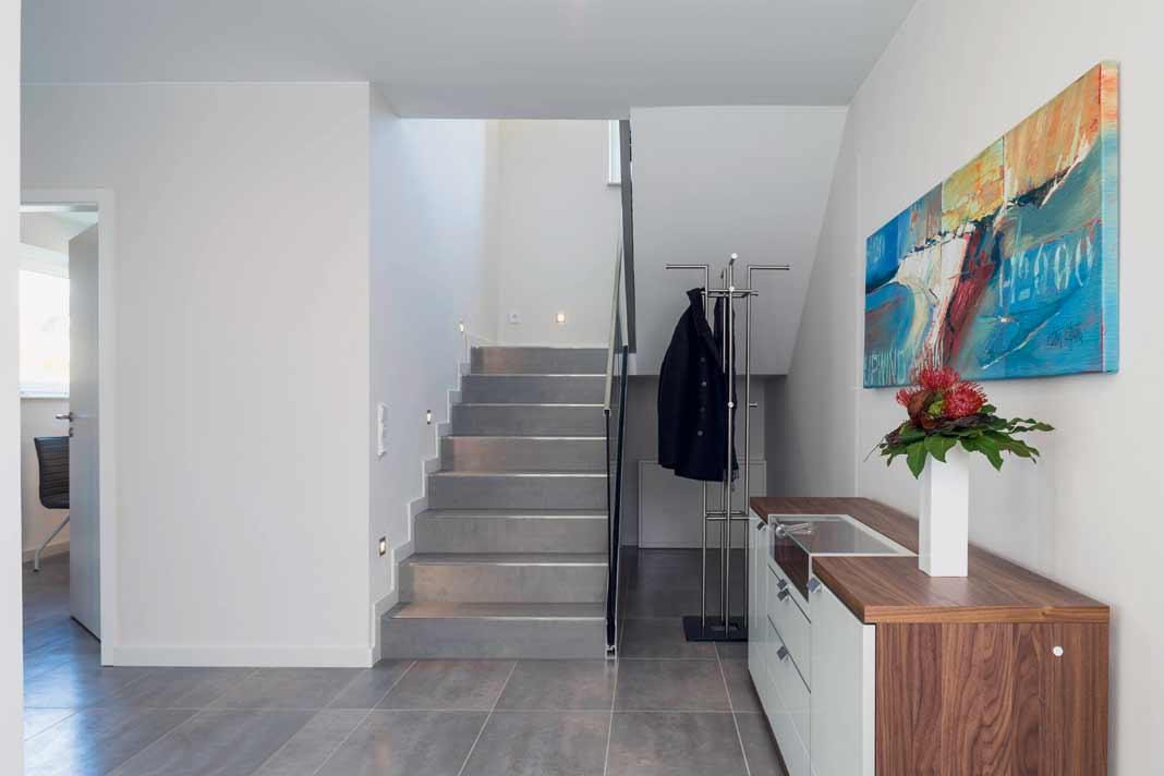 Über eine elegante Steintreppe gelangt man ins Obergeschoss. Foto: Arge