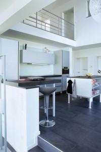 """Über der Küche öffnet sich der Luftraum mit Galerie – keinesfalls """"verschenkter"""" Platz, sondern Maximierung von Freiraum und Wohngefühl. Foto: Ringen Architektur"""