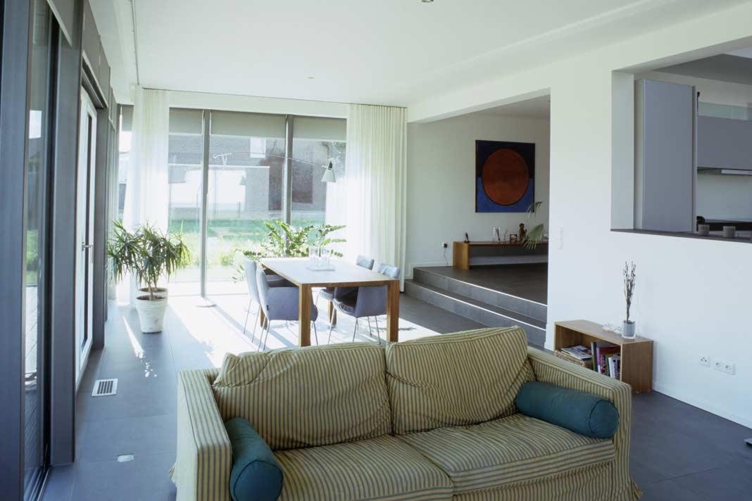 Sofa-Ecke, Essplatz und Küche gehen offen ineinander über, wobei der Niveauunterschied von zwei Stufen eine bauliche Abgrenzung der Funktionsbereiche zart andeutet. Foto: Rongen Architektur