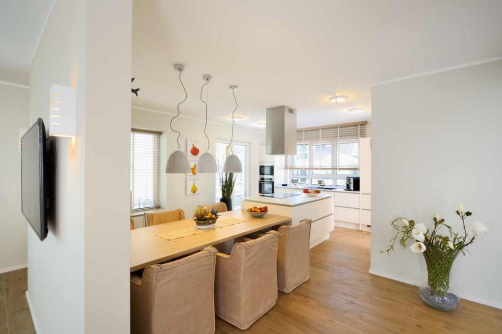 Eine Wandscheibe trennt den Essplatz optisch vom Wohnbereich und schafft so einen Rückzugsbereich für die Familie, ohne den offenen Grundriss aufzugeben. Foto: Repo