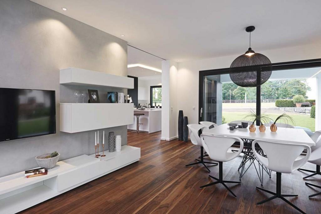 Der Wohn- und Essbereich geht übergangslos in die Küche über. Auf Wunsch können die Räume mit einer Schiebetür vonein - ander getrennt werden. Foto: WeberHaus