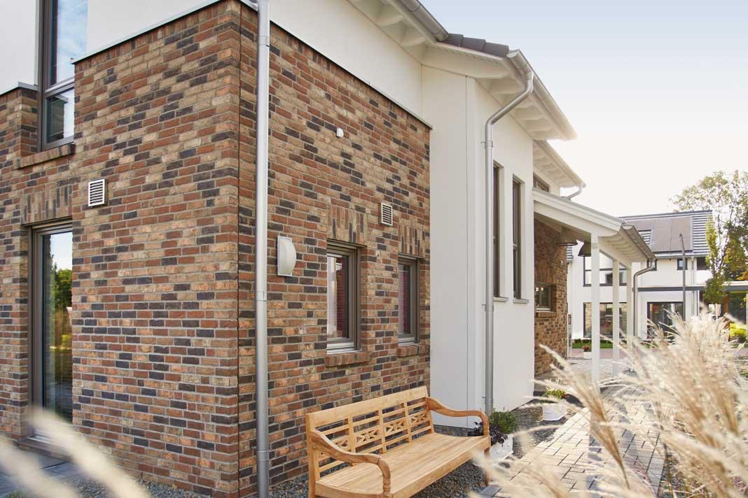 Schon das Entrée wirkt repräsentativ: Vom traufhohen, weiß verputzten Erker und dem sich seitlich anschließenden Vordach vor Wind und Wetter geschützt, lädt die Haustür zum Betreten des Hauses ein.