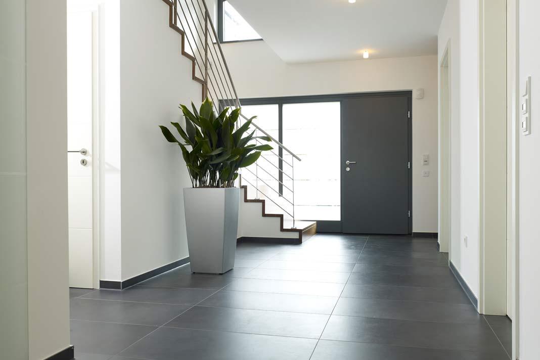Das moderne Stadthaus mit quadratischem Grundriss verfügt über einen Windfang mit exklusiver Haustür, was stilvolles Ankommen verspricht.