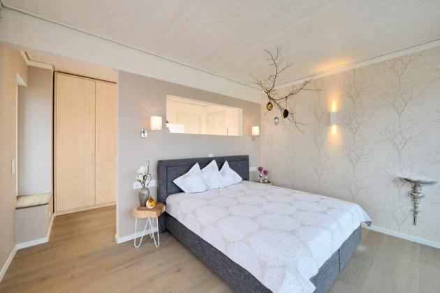 Die Wandscheibe mit Glaseinsatz am Kopfende des Bettes ist ein spannendes Detail und sorgt für Licht im hinteren Schrankbereich.