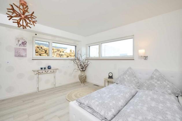Die hoch liegenden Fensterbänder im Schlafzimmer der Einliegerwohnung lassen viel Licht in den Raum.