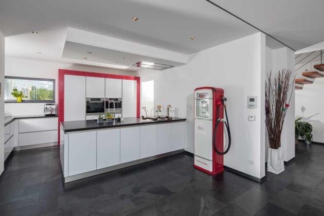 Die Zapfsäule ist der Hingucker in der modernen, farbenfrohen Küche, die nahtlos in die Wohndiele übergeht.
