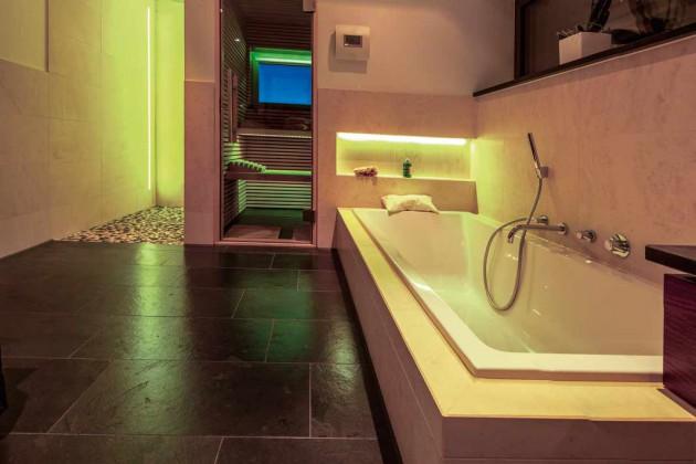Badezimmer als kleine Wellnessoase mit Sauna und Whirlwanne.