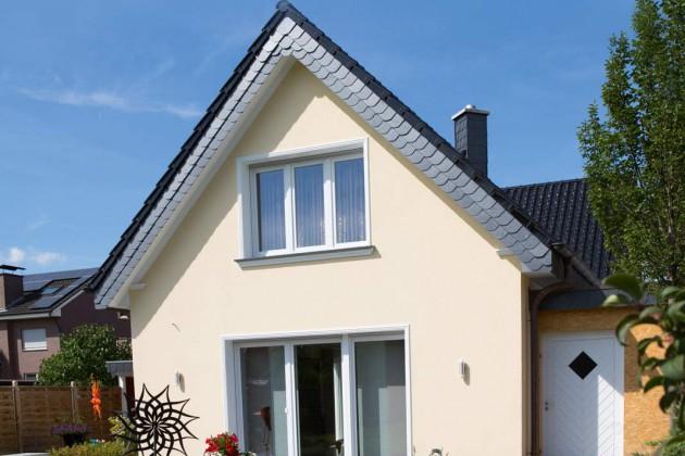 Der beigefarbene Hausanstrich und die weißen Fassadenprofile harmonieren perfekt.