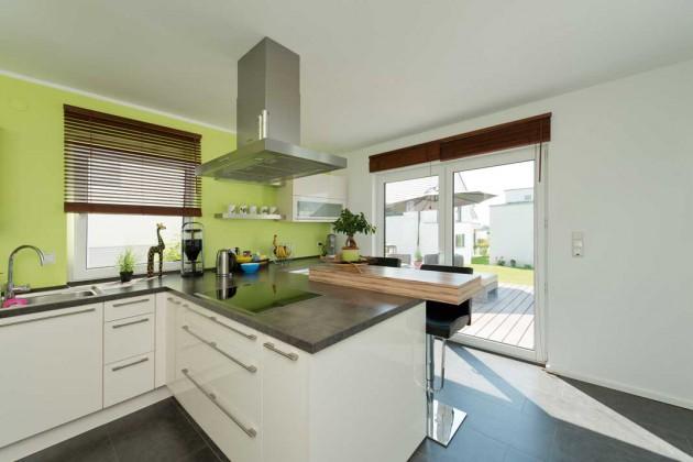 Auch in der Küche sorgen bodentiefe Fensterelemente für reichlich Tageslichteinfall. Eine lindgrüne Wand bringt Farbe ins Spiel.
