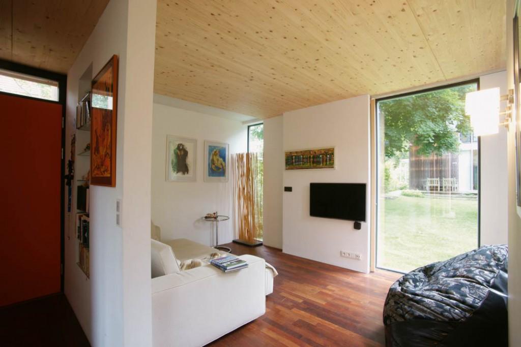 Durch die großen Panoramafenster des Wohnbereichs reicht der Blick bis in den Garten und zum Elternhaus.