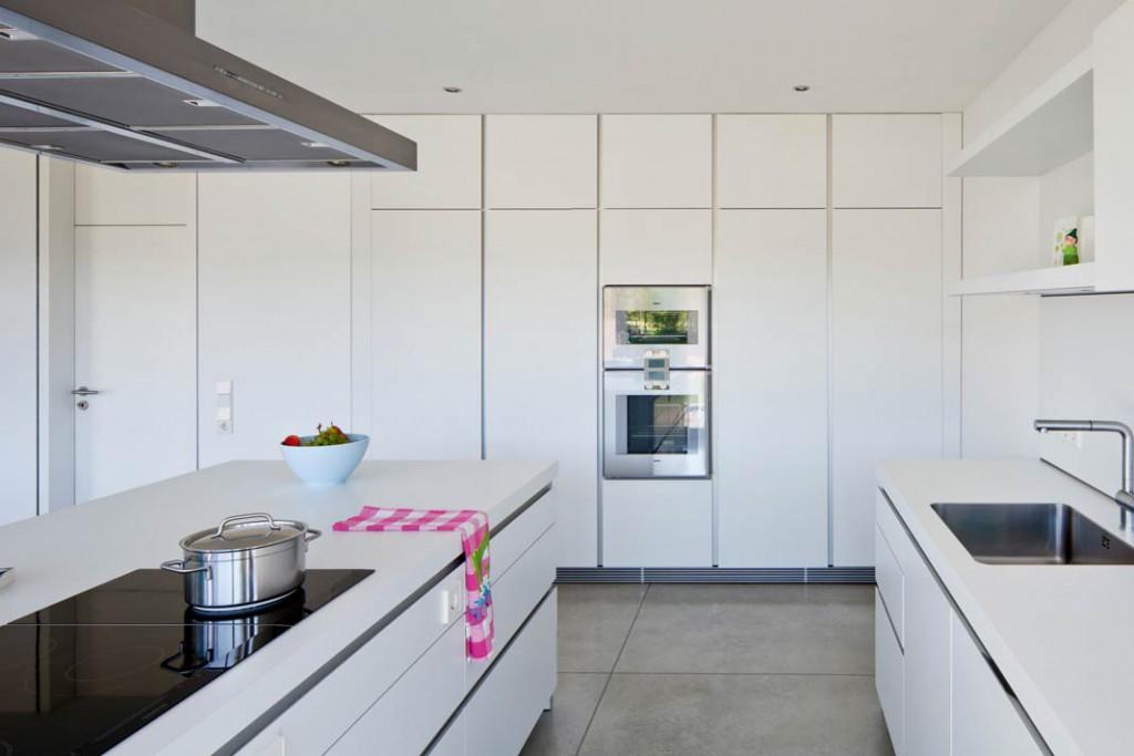Die großzügige, offene Küche wurde ganz in Weiß gehalten, was ihren modernen Charakter betont.