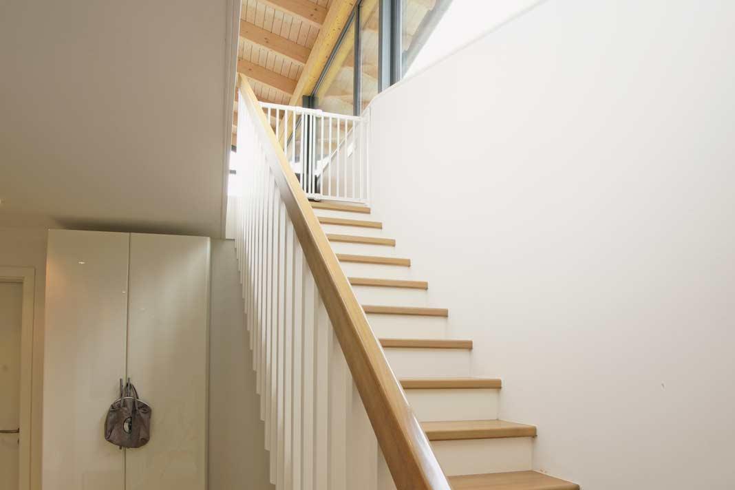 Eine geradläufige Holztreppe verbindet den Wohnbereich und Elternbereich oben mit den beiden Kinderzimmern sowie dem Kinderbad auf der unteren Etage.