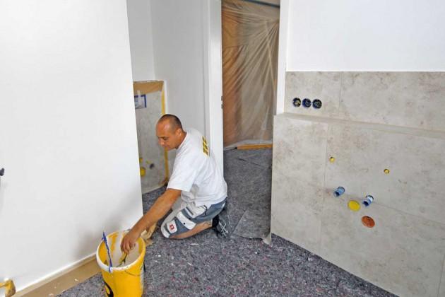 Nach den Fliesenarbeiten kommt der Maler und weißelt die nicht gefliesten Wandbereiche.