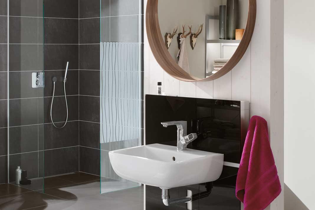 Die Sanitärinstallationselemente mit der farbigen Glasfront dienen gleichzeitig als Badmöbel mit einem seitlichen Auszug.
