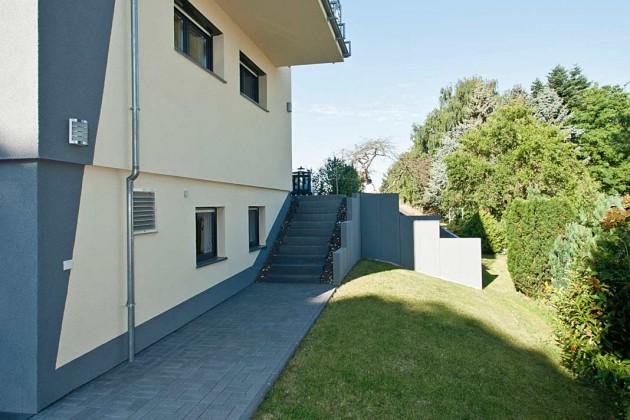 Die seitliche Erschließung am Haus entlang mit den Stützmauern führt die steile Hanglage des Grundstücks vor Augen.