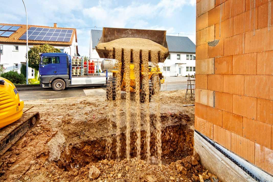 Die Grube für den Flüssiggasbehälter wird mit einem Bagger ausgehoben.