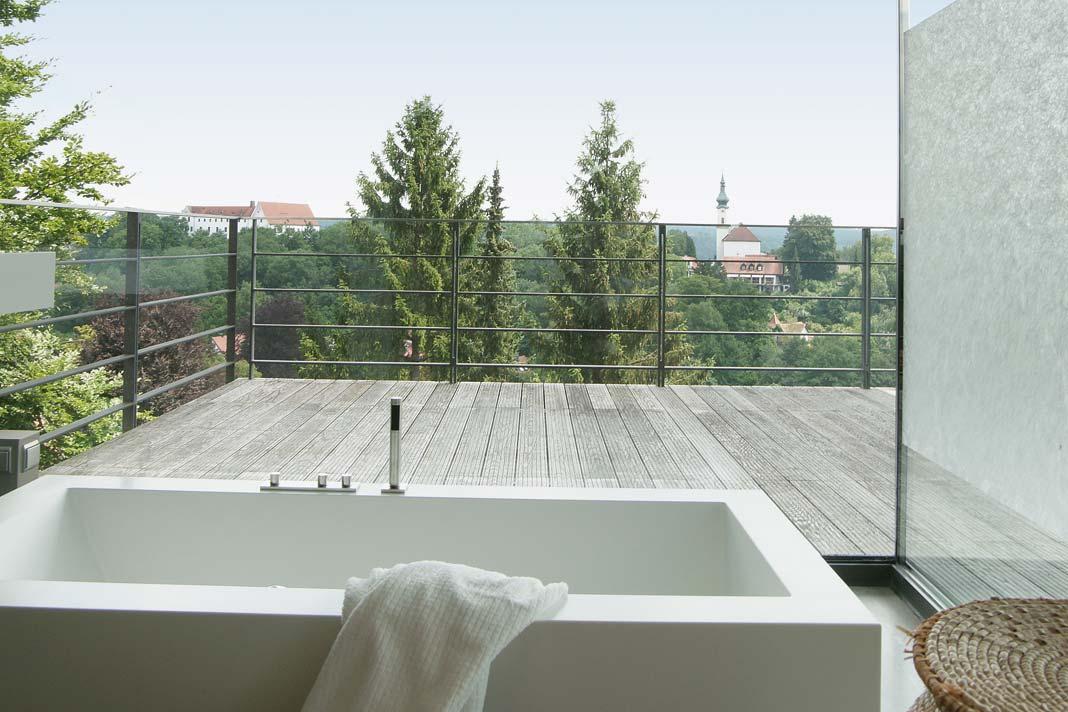 Raumhohe Verglasungen geben auch beim Wannenbad den Blick auf die Terrasse frei.
