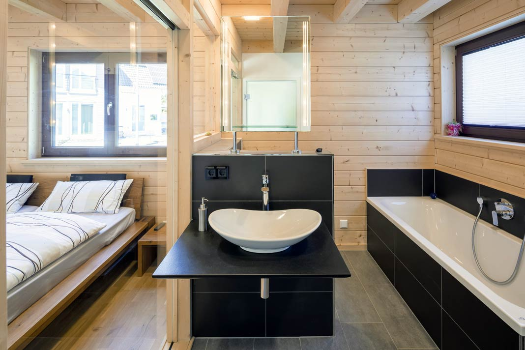 Eine Glasscheibe trennt den Schlafbereich vom Badezimmer.