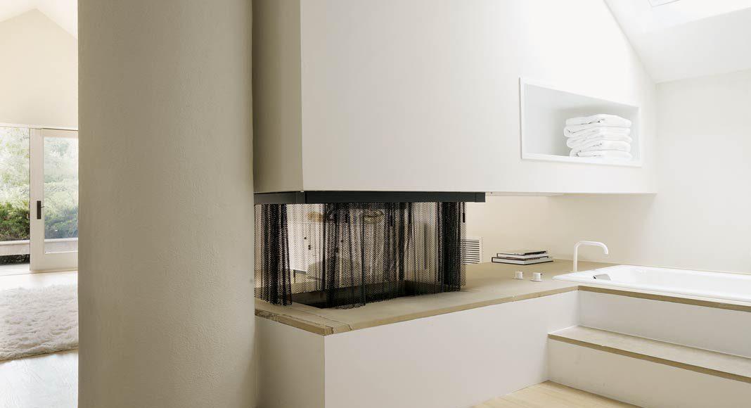 Eine Wandscheibe mit offenem Kamin dient als optische Abtrennung.