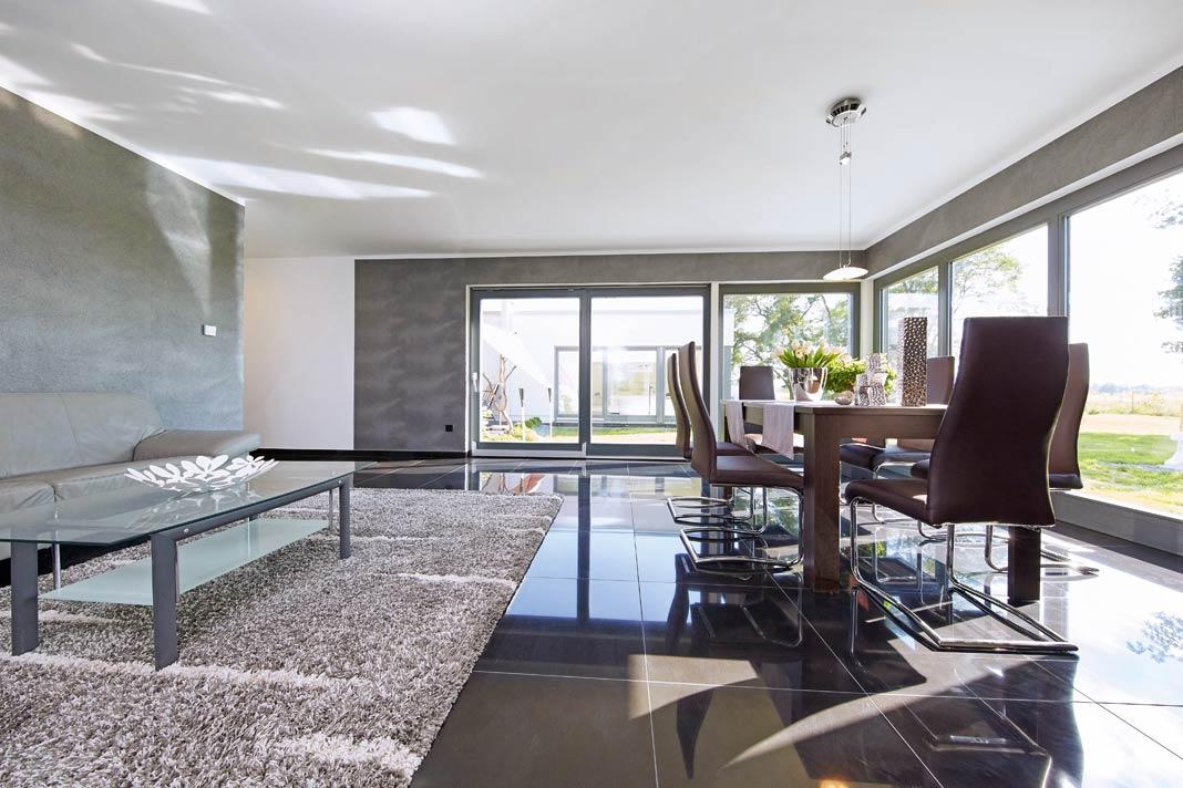 Vom Essplatz aus kann der Blick auf die Terrasse, in den Garten und bis ins gegenüberliegende Schlafzimmer schweifen.