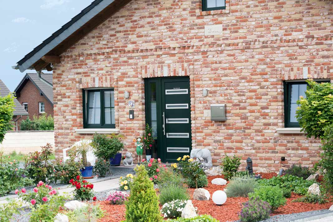 Die grünen Fenster und die Haustür harmonieren perfekt mit der Natur.
