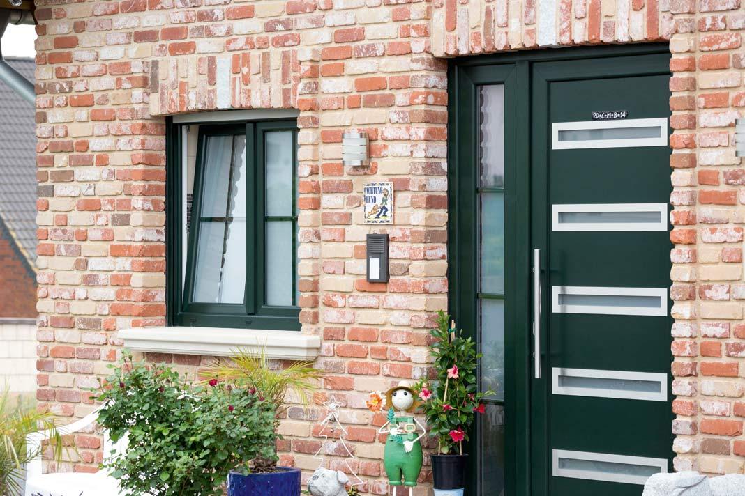 In diesem Einfamilienhaus wurden Türen und Fenster bewusst in Dunkelgrün eingebaut, was für einen ersten Blickfang sorgt.