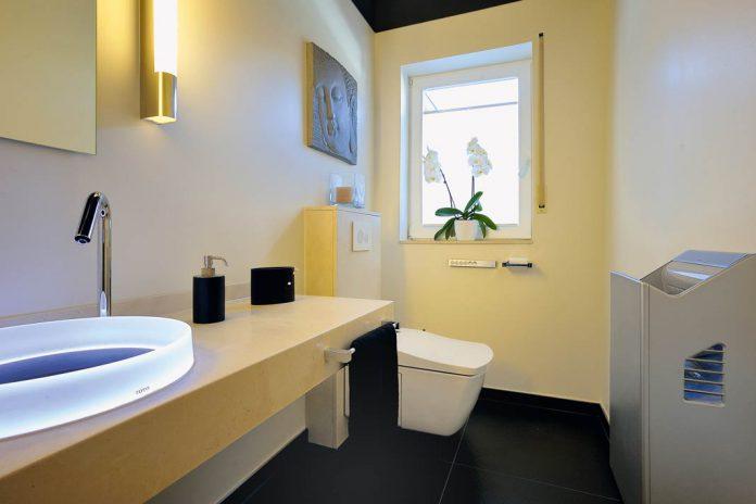 Gäste-WC mit sensorgesteuertem Deckel, temperiertem Sitz und einer Intimreinigung mit Wasserstrahl.