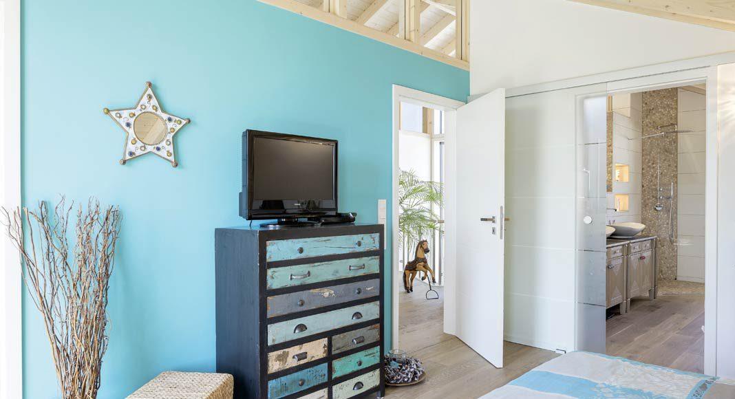 Als Kontrast zu dem hellen Holzton und den weißen Wänden findet sich im Schlafzimmer ein kräftiger Türkis-Ton.