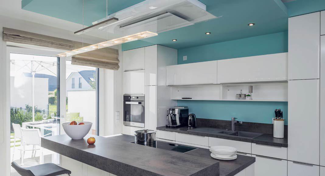 Eine Wandscheibe trennt die Küche optisch vom Ess- und Wohnbereich ab.