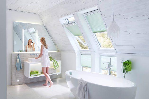 Ganz in hellem, skandinavischem Stil gehalten ist dieses Bad im Dachgeschoss. Grüne Farbakzente setzen Accessoires sowie der Sicht- und Sonnenschutz. Foto: Velux Deutschland GmbH